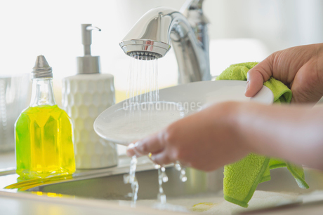 Woman rinsing white plate in kitchen sink.の写真素材 [FYI02290406]