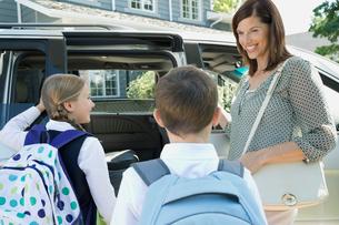 Mother watching kids get into minivanの写真素材 [FYI02290446]