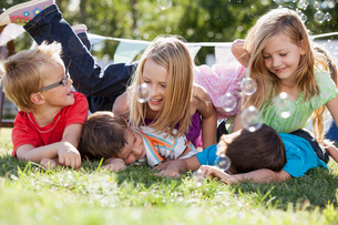 Cousins piling up on the lawn outdoors.の写真素材 [FYI02290460]