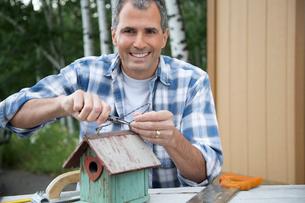 portrait of middle-aged man repairing birdhouseの写真素材 [FYI02290489]