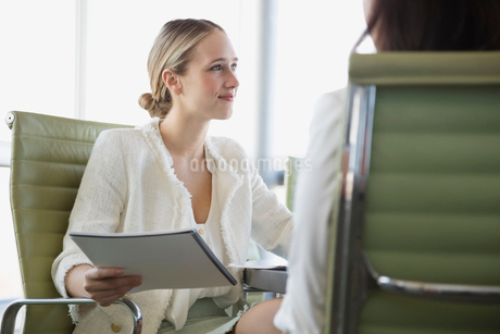Young businesswoman looking away while holding file in officeの写真素材 [FYI02290511]