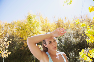 Woman wiping brow during outdoor workout.の写真素材 [FYI02290518]