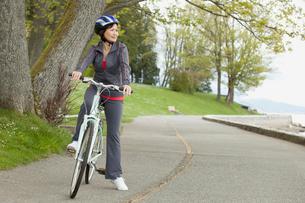 mature woman riding bike in parkの写真素材 [FYI02290581]
