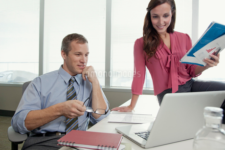 coworkers reviewing plans on laptopの写真素材 [FYI02290652]