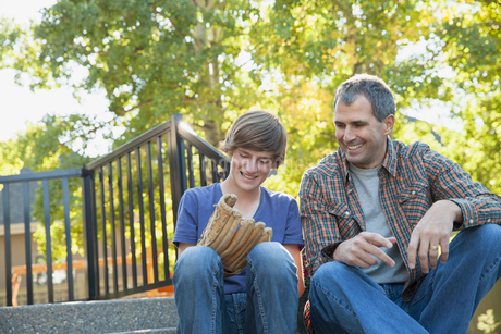 Happy father looking at son wearing baseball glove in yardの写真素材 [FYI02290684]