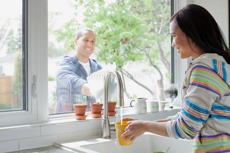 latino couple washing the kitchen windowの写真素材 [FYI02290726]