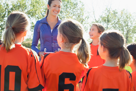 View from behind of girls soccer team listening to coach.の写真素材 [FYI02290836]