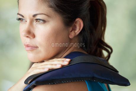 woman applying heat to sore muscleの写真素材 [FYI02290860]