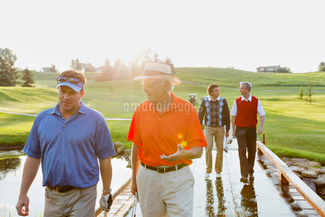 foursome of make golfers walking across bridge on fairwayの写真素材 [FYI02290873]