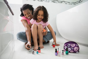 Mother painting daughter's toenails in bathroomの写真素材 [FYI02290881]