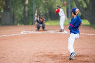 Young baseball pitcher winding up to throw baseball.の写真素材 [FYI02290923]