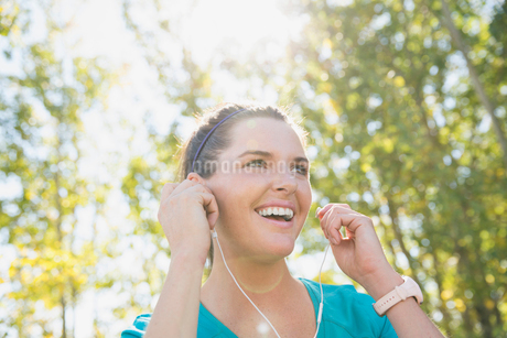 Woman smiling while listening to music outdoors.の写真素材 [FYI02290989]