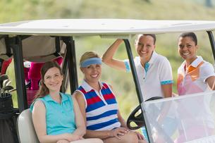 portrait of four female golfers by golf cartの写真素材 [FYI02291004]