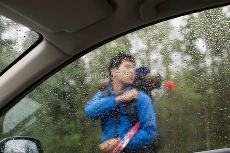 view of male hiker through car windowの写真素材 [FYI02291015]