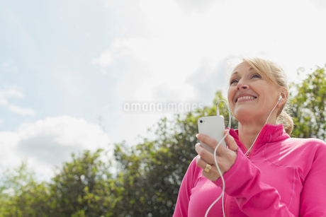Senior woman listening to music on smartphone in theの写真素材 [FYI02291029]