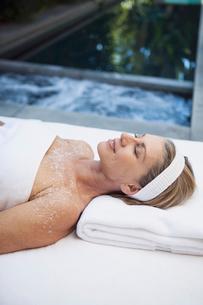 middle aged woman enjoying salt scrub treatmentの写真素材 [FYI02291119]