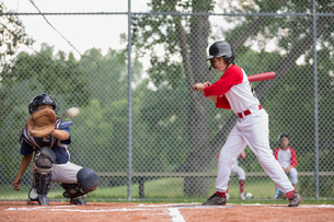 Young ball player watching pitch go past the plate.の写真素材 [FYI02291122]