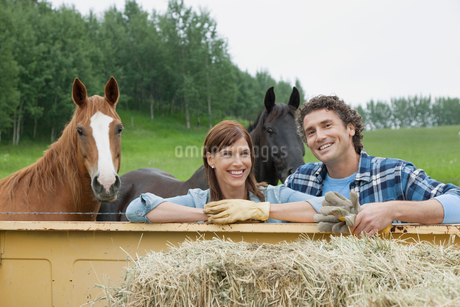 middle-aged couple standing by truck with two horsesの写真素材 [FYI02291158]