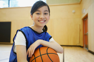 Female, middle school student posing with basketball.の写真素材 [FYI02291245]