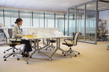 Businesswoman reading book at deskの写真素材 [FYI02291250]