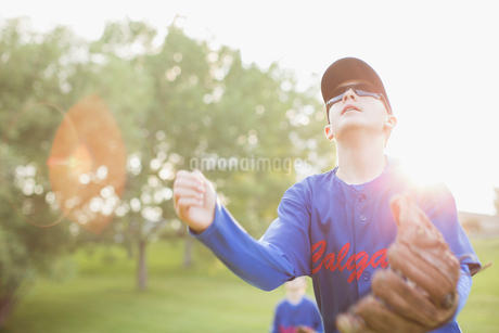 Young baseball player looking up for fly ball.の写真素材 [FYI02291275]