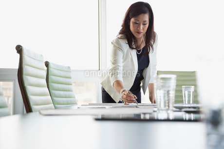 Businesswoman making notes on blueprint at conference tableの写真素材 [FYI02291383]