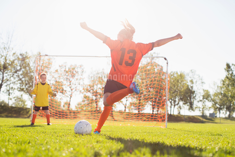 Young female soccer player about to kick soccer ball.の写真素材 [FYI02291394]