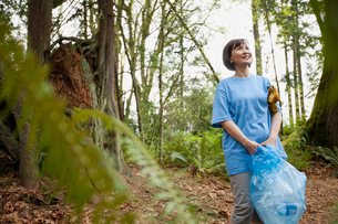 mature woman helping to clean up parkの写真素材 [FYI02291410]