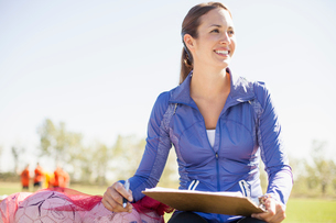 Female soccer coach sitting on bench with clipboard.の写真素材 [FYI02291417]
