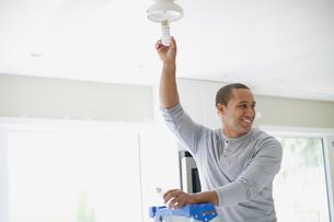 young adult latino man replacing light bulbの写真素材 [FYI02291445]