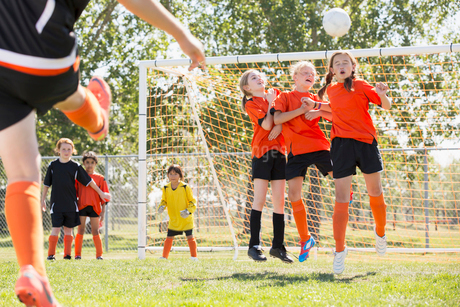 Young soccer player defending her net with a header.の写真素材 [FYI02291465]