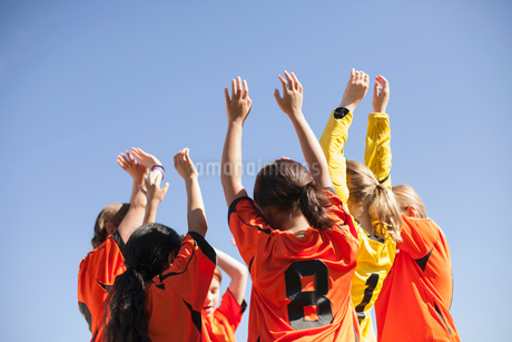 Soccer girls with arms raised in a cheer.の写真素材 [FYI02291495]