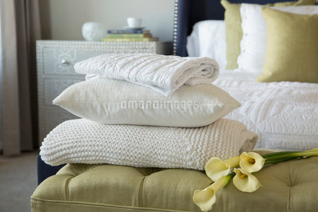 Pillow, blankets and lilies on footstool in bedroomの写真素材 [FYI02291520]