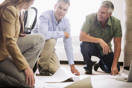office workers reviewing plans on office floorの写真素材 [FYI02291527]