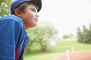 Twelve year old baseball player watching game from bench.の写真素材 [FYI02291543]