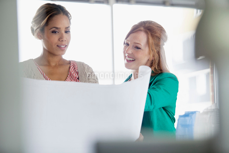 female office workers reviewing plans togetherの写真素材 [FYI02291569]