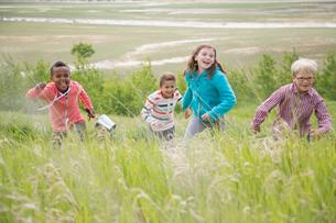elementary aged children running in grasslandの写真素材 [FYI02291594]