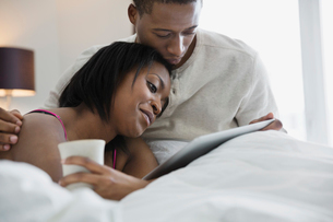 Relaxed couple sharing digital tablet in bedの写真素材 [FYI02291597]
