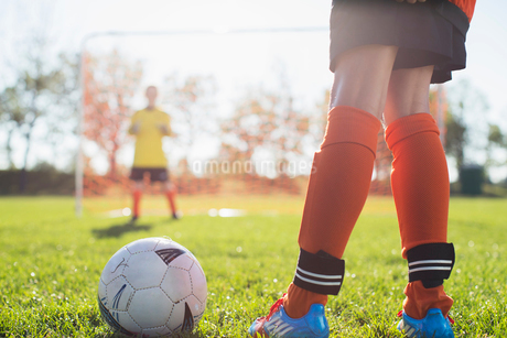 Young female soccer player with ball in front of net.の写真素材 [FYI02291618]
