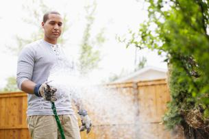 young adult man watering gardenの写真素材 [FYI02291620]