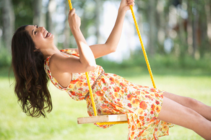 mid-adult woman laughing on outdoor swingの写真素材 [FYI02291697]
