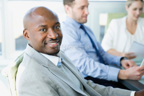 Businessman sitting in office with colleagues in backgroundの写真素材 [FYI02291777]