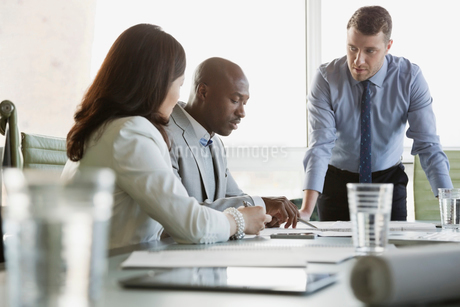 Businessman reviewing blueprint with colleagues at conference tableの写真素材 [FYI02291788]