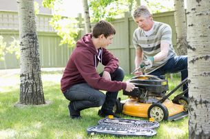 father and son maintaining lawn mowerの写真素材 [FYI02291918]