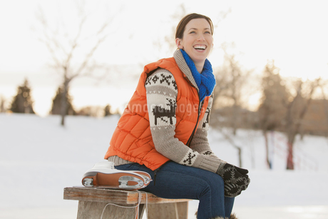 Cheerful woman putting on ice skatesの写真素材 [FYI02291997]