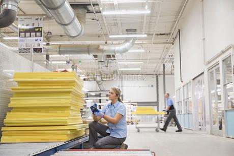 Worker examining insulation in factoryの写真素材 [FYI02292004]