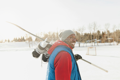 Smiling man walking with ice skates and hockey stickの写真素材 [FYI02292116]