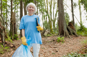 mature woman helping to clean up parkの写真素材 [FYI02292119]