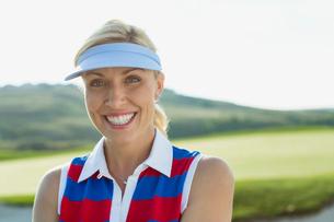 portrait of pretty, mid-adult female golfer with sun visor onの写真素材 [FYI02292152]