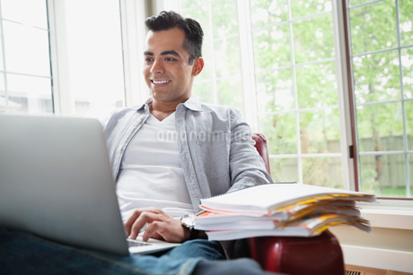 Man using laptop while sitting on couch at homeの写真素材 [FYI02292160]